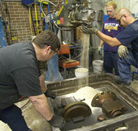Metal casting students collaborating during the sand casting process