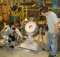 UNI metal casting students pouring metal into molds